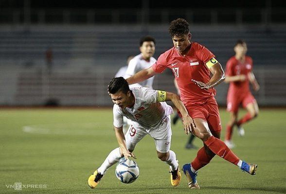 Pha va chạm khiến Quang Hải (áo trắng) bị rách cơ đùi trái  trong trận Việt Nam thắng Singapore, vòng bảng SEA Games 30. Ảnh: Đức Đồng