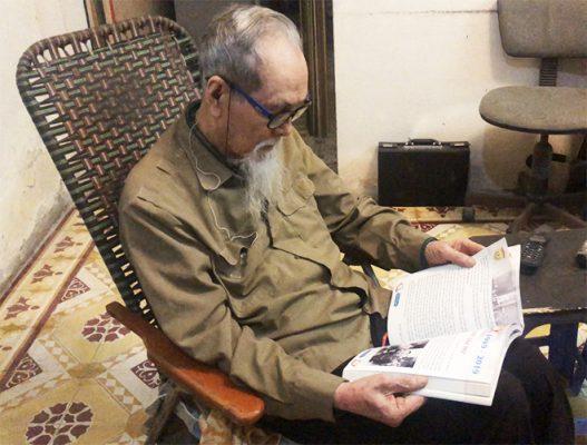 Ông Hùng đọc sách, báo và nghe đài mỗi ngày để cập nhật kiến thức mới rồi phổ biến cho mọi người. Ảnh: Thùy An