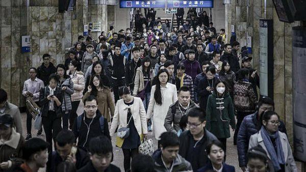 Các nhân viên văn phòng tại một bến tàu điện ngầm ở Trung Quốc. Ảnh:Bloomberg