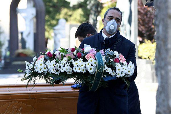 Một nhân viên tang lễ vận chuyển hoa gửi chomột nạn nhân Covid-19 đến một nghĩa trang ở thành phố Bergamo, miền bắc Italy. Ảnh: Reuters.