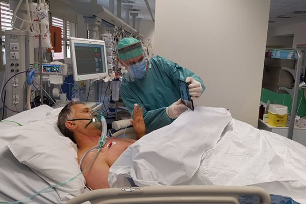 Bệnh nhân Covid-19 trong phòng chăm sóc đặc biệt nói chuyện với người thân qua cuộc gọi trực tuyến. Ảnh: NYT.